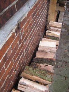 Ruimte tussen muur en hout en het hout van de grond om drogen te stimuleren.